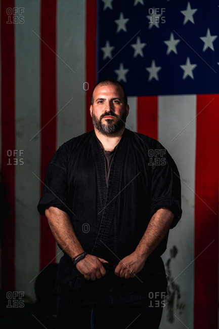 Serious bearded adult martial arts master in black uniform standing against American flag and looking at camera