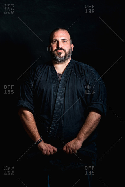 Serious bearded adult martial arts master in black uniform standing against black background and looking at camera