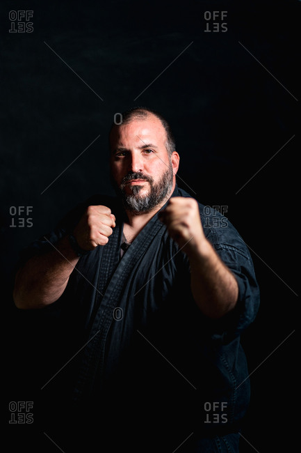 Confident adult bearded martial arts practitioner with tattooed arms standing in defensive fighting pose against black background