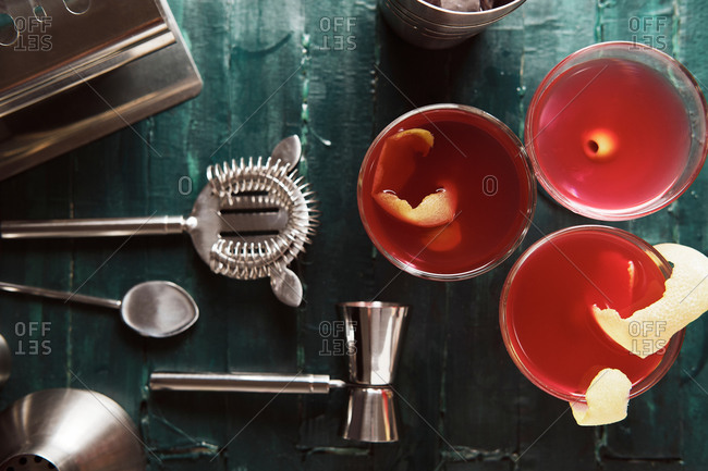 From above set of coupe glasses with red alcohol cocktail garnished with green olive and lemon peel served on counter in bar