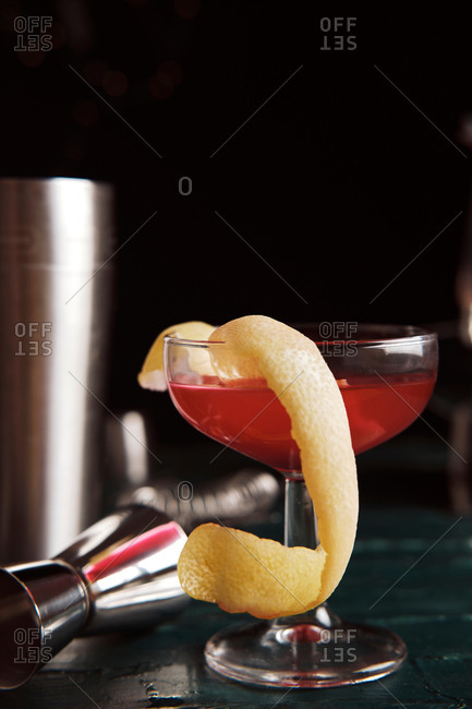 Front view set of coupe glasses with red alcohol cocktail garnished with green olive and lemon peel served on counter in bar