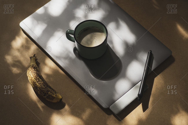 From above composition with mug of coffee placed on pen graphic tablet near ripe banana on light brown table in sunny room