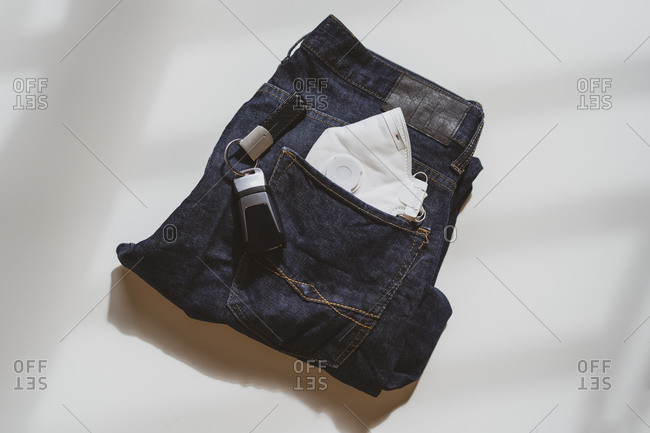 From above of folded jeans with white protective mask in pocket and car keys placed on white background in light studio
