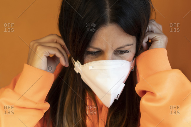 Young female in casual orange jacket putting on white protective mask against orange background