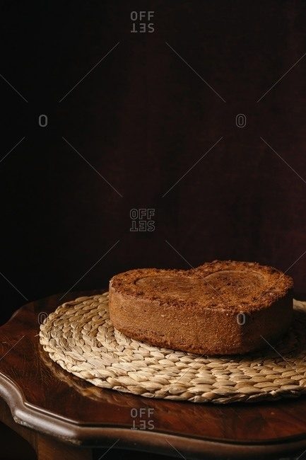 From above of freshly baked homemade sweet cake in shape of heart placed on round wicker placemat on wooden table background