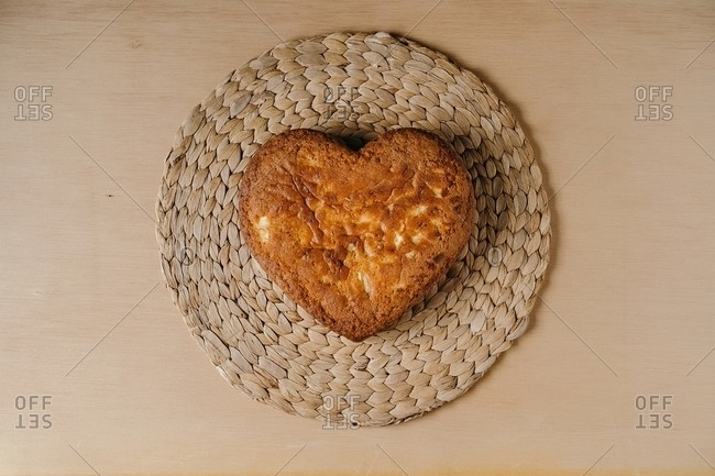 From above of freshly baked homemade sweet cake in shape of heart placed on round wicker placemat