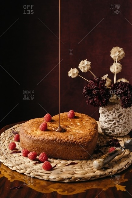 Appetizing homemade cake with fresh berries being poured with chocolate topping placed on wicker tray on table with flowers