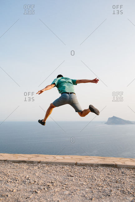 Low angle back view of unrecognizable male in casual clothes jumping high against blue sky and sea during summer evening