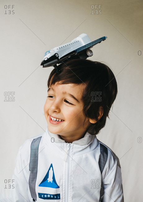 Positive child wearing spaceman uniform standing with toy spaceship on top of his head and cheerfully smiling away