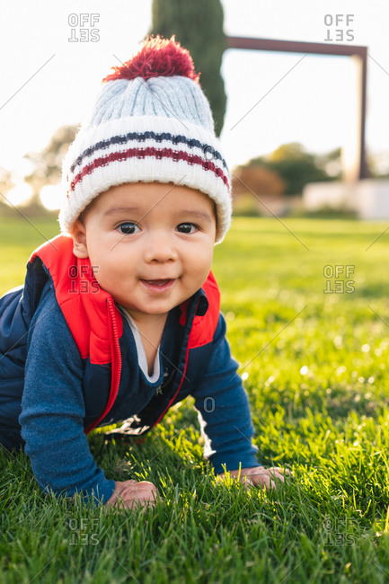 Cute ethnic toddler in warm clothes smiling and looking at camera while crawling on green meadow during family weekend in countryside