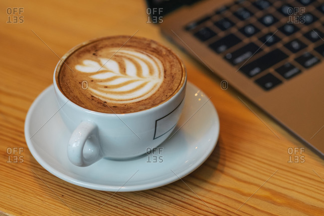 High angle of white ceramic cup of yummy hot cappuccino on brown wooden table beside blurred laptop in modern cafe