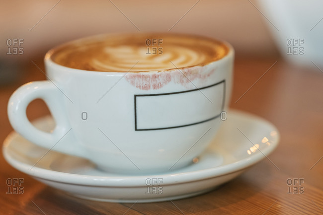 High angle of white ceramic cup of yummy hot cappuccino covered in red lipstick marks on brown wooden table
