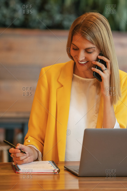 Adult overjoyed businesswoman in formal wear looking away and laughing while talking on phone sitting at wooden table with laptop and taking notes in notebook in contemporary office