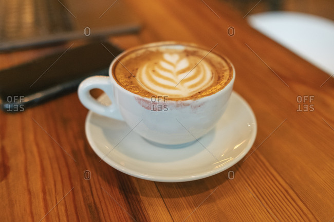 High angle of white ceramic cup of yummy hot cappuccino covered with red lipstick marks on brown wooden table beside blurred smartphone in modern cafe