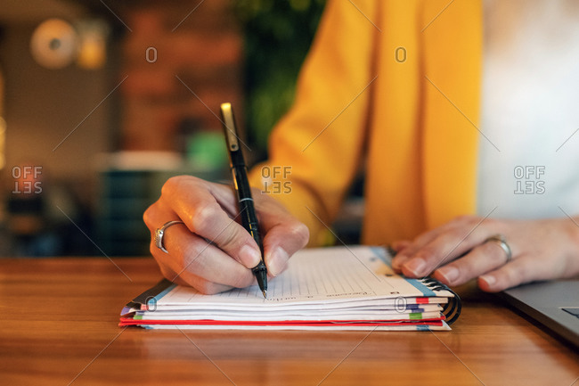 Crop unrecognizable businesswoman in elegant colorful clothes writing with pen in notebook while sitting at wooden table and using laptop in light contemporary office