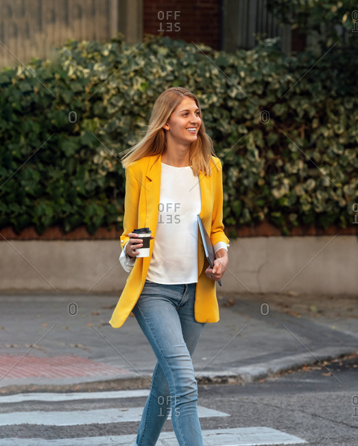 Trendy slim blond businesswoman walking along pedestrian crossing against exteriors of residential multistory buildings and cars parked on street in downtown