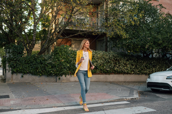 Trendy slim blond businesswoman looking away in elegant vivid yellow jacket and jeans with digital tablet against exteriors of residential multistory buildings and cars parked on street in downtown