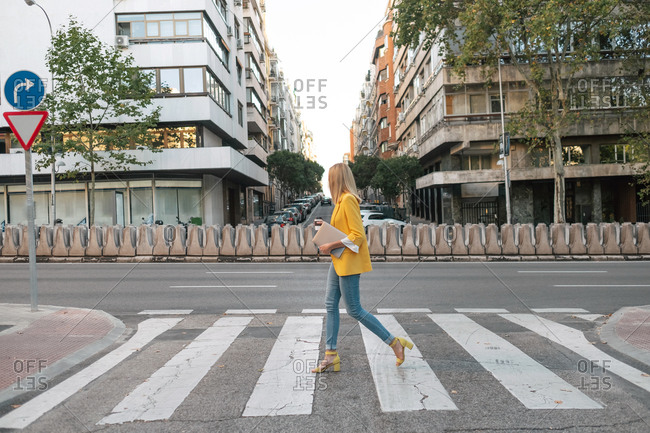 Side view of trendy slim blond female in elegant vivid yellow jacket and jeans with digital tablet walking alone along pedestrian crossing against exteriors of residential multistory buildings and cars parked on street in downtown