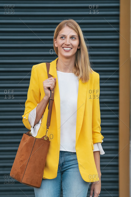 Happy young blond female in bright yellow jacket and jeans with brown handbag over shoulder smiling away while standing on street against blurred striped wall in city