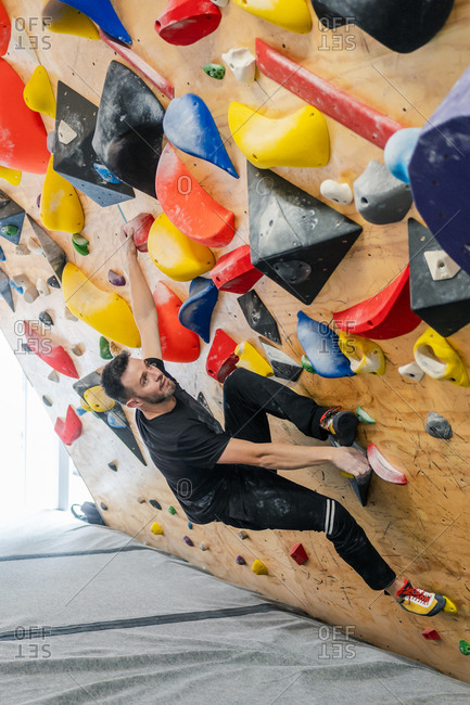 From bellow strong male athlete in sportswear climbing on colorful wall during workout in modern guy