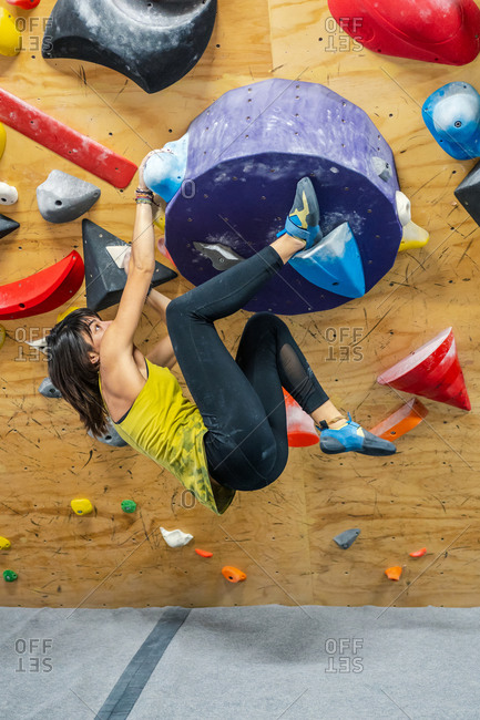 Strong young black haired female climber in active wear smiling while hanging on big grip of climbing wall in gym