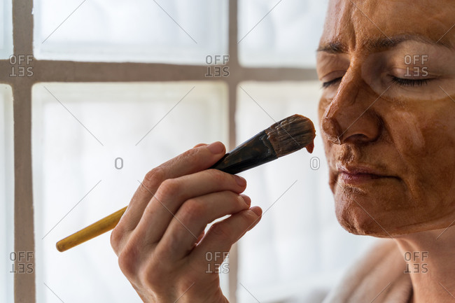 Side view of adult female standing with closed eyes in bathrobe and towel turban while putting hydrating cosmetic mask on face with brush