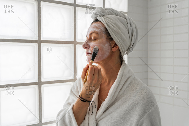 Side view of female putting moisturizing mask on face with cosmetic brush while taking care of skin