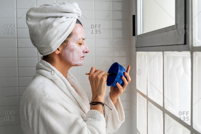 Side view of calm female in white bathrobe and towel turban applying clay mask with brush while standing in bright bathroom