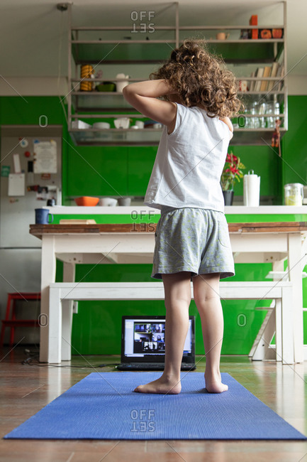 Back view of little girl in activewear learning balance yoga asana while practicing in front of laptop at home