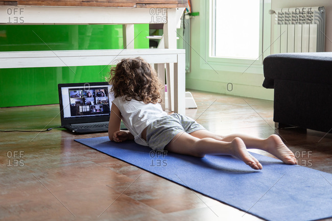 Back view of unrecognizable little girl watching online video tutorial on laptop while sitting on mat and learning yoga pose at home