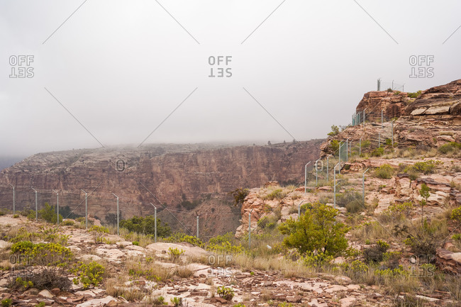 Breathtaking view of rough rocky cliff with green shrubs and metal barrier located in mountainous terrain on misty day