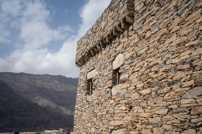 Exterior of ancient stone wall of historic building of Marble Village in Al Bahah against background of rocky terrain and cloudy sky in summer in Saudi Arabia