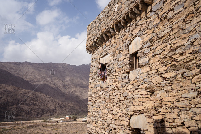 Woman leaning out of a window of ancient stone wall of historic building of Marble Village in Al Bahah against background of rocky terrain and cloudy sky in summer in Saudi Arabia