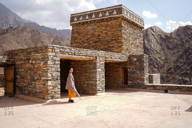 monumental ancient building with remote female tourist coming out of doorway in yellow dress while enjoying hot sunny day in Marble Village in Al Bahah