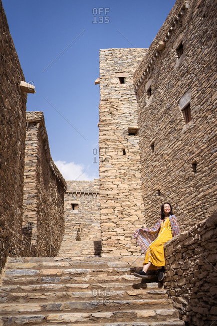 From below of monumental ancient building with remote female tourist coming out of doorway in yellow dress while enjoying hot sunny day in Marble Village in Al Bahah