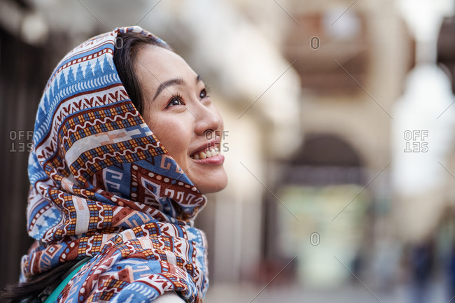 Young ethnic female in headscarf smiling and looking away while standing against blurred urban background in Jeddah city in Saudi Arabia
