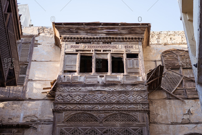 Low angle of aged stone buildings with shabby walls and balconies on street of Jeddah city in Saudi Arabia