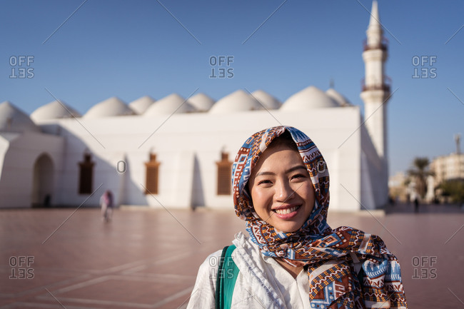 Happy young Asian female in traditional headscarf smiling and looking at camera while standing on square against Islam mosque in Jeddah city in Saudi Arabia