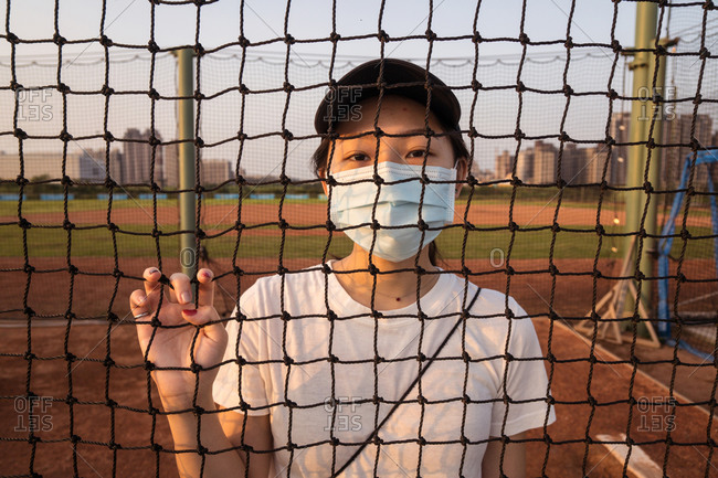 Young ethnic female in sportswear and protective mask for coronavirus prevention looking at camera through net fence while standing on empty sports ground in city