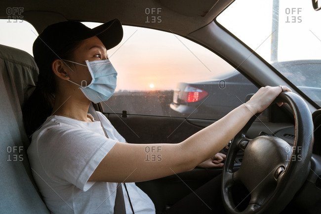 Side view of young Asian female in casual clothes and protective mask for coronavirus prevention driving car