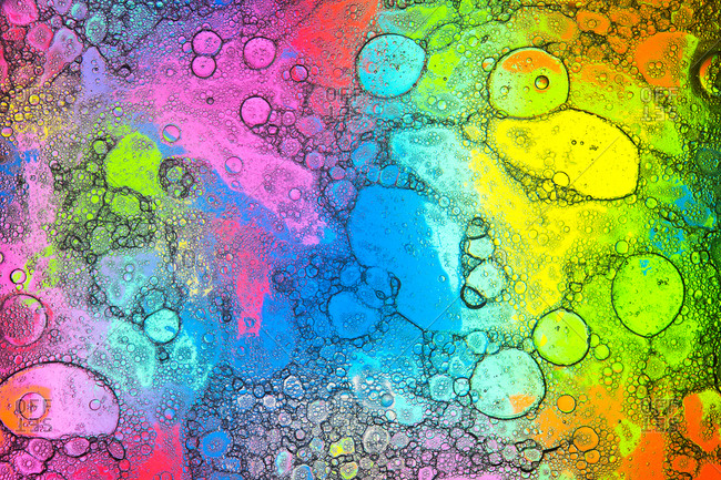 Top view of transparent soap bubbles covering colorful background with vivid geometric stains
