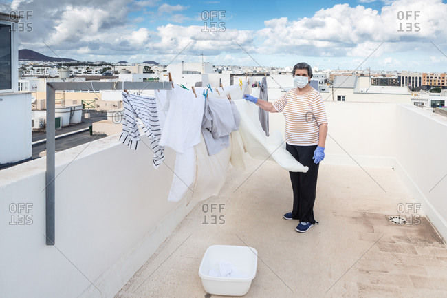 Elderly woman looking at camera in casual clothes wearing protective mask and latex gloves hanging laundry on rope on outdoor terrace of house on cloudy day