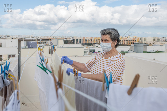 Side view of adult woman in casual clothes wearing protective mask and latex gloves hanging laundry on rope on outdoor terrace of house on cloudy day