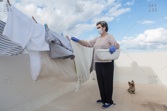 Side view of adult woman in casual clothes wearing protective mask and latex gloves holding plastic basin and taking laundry off the rope on outdoor terrace of house on cloudy day