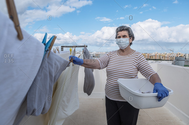 Elderly woman looking at camera in casual clothes wearing protective mask and latex gloves holding plastic basin and taking laundry off the rope on outdoor terrace of house on cloudy day