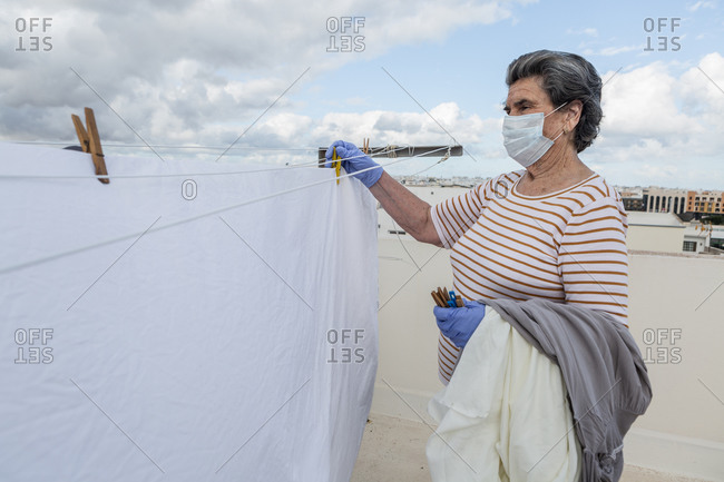 Side view of adult woman in casual clothes wearing protective mask and latex gloves taking laundry off the rope on outdoor terrace of house on cloudy day