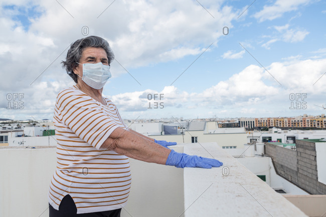 Thoughtful elderly woman in protective mask and gloves standing by the edge of a roof terrace fence looking at the camera