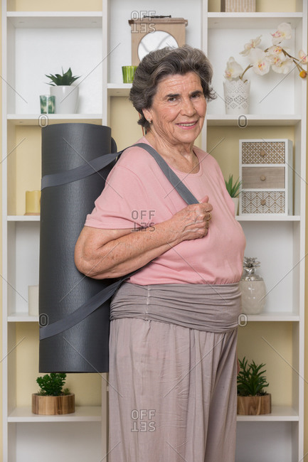 Content senior adult woman in casual clothes standing with rolled yoga mat near shelves in room and looking at camera