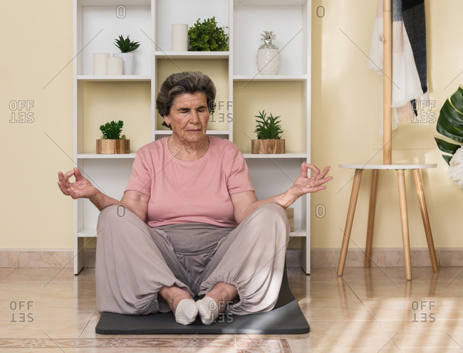 Concentrated senior female in activewear sitting on mat near shelves and meditating with closed eyes during yoga practice at home