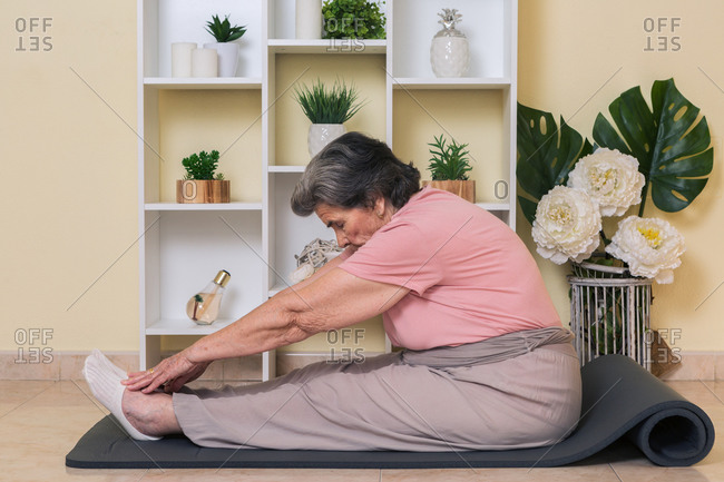 Side view of elderly lady in active wear sitting on mat near shelves with potted plants in room and doing stretching exercise during yoga training